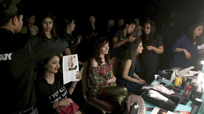 """Models backstage prepare to present designer's creations during """"Fashion Pakistan Weeks Winter Festive 2015,"""" in Karachi, Pakistan, Saturday, Nov. 28, 2015. More than twenty designers are participating in the three-day event to showcase their latest collections. (AP Photo/Shakil Adil)"""