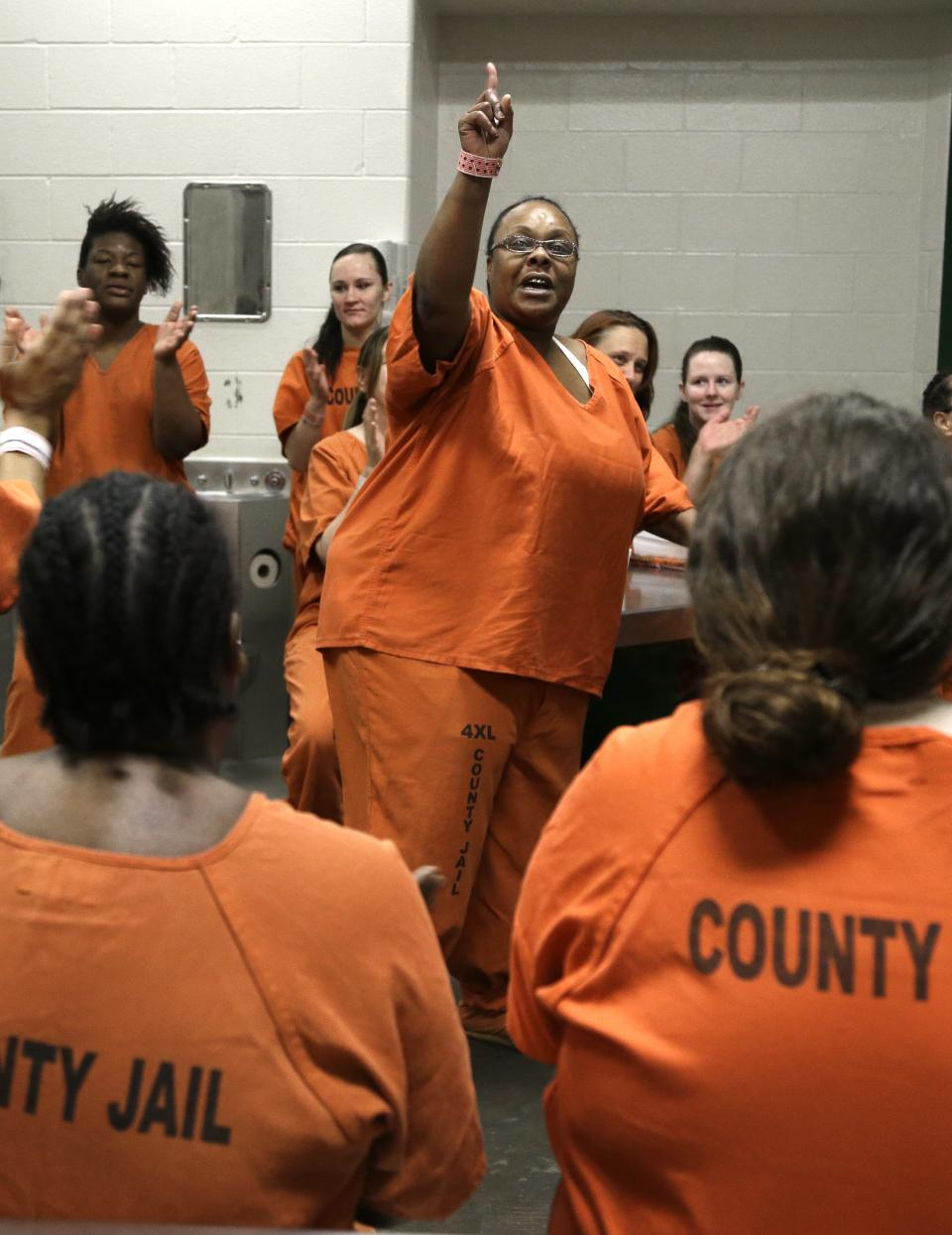 Lisa Riles, center, leads a cheer during a group meeting in their Harris County jail cell Tuesday, June 4, 2013, in Houston. The women participate in a prostitution rehabilitation program We've Been There Done That. (AP Photo/Pat Sullivan)