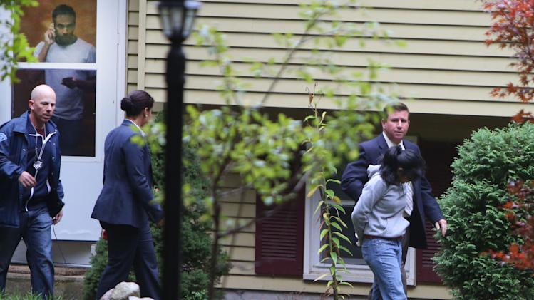 Family member, left, watches as Annie Dookhan, right, is escorted to a cruiser outside her home in Franklin, Mass., Sept. 28, 2012. Dookhan is accused of faking drug results, forging signatures and mixing samples at a state police lab.  State police say Dookhan tested more than 60,000 drug samples involving 34,000 defendants during her nine years at the lab. Defense lawyers and prosecutors are scrambling to figure out how to deal with the fallout. (AP Photo/Bizuayehu Tesfaye)