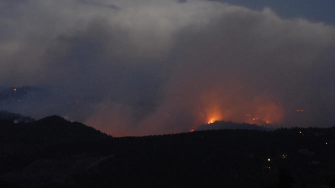 Leaping flames race across a ridge as the Waldo Canyon Fire burned 2500 acres west of Garden of the Gods near Colorado Springs, Colo. on Saturday, June 23, 2012.  The fire is zero percent contained. Voluntary and mandatory evacuations were taking place across the west side of Colorado Springs.  Tankers were dropping fire retardant in front of the advancing flames.  ( AP Photo/Bryan Oller)