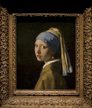 This reproduction shows Johannes Vermeer's Girl with a Pearl Earring (painted approximatetely 1665) at the renovated Mauritshuis museum during a preview for the press in The Hague, Netherlands, Friday, June 20, 2014. The Mauritshuis reopens after a two-year renovation that allowed its masterpieces, including Vermeer's The Girl with the Pearl Earring to be seen by record-setting crowds abroad. The public will have access for free from 8 pm till midnight on Friday June 27th after the official ceremonial opening and from June 28 onwards the museum will revert to regular opening hours. (AP Photo/Peter Dejong)