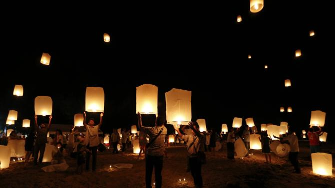 Survivors, local residents and visitors release paper lanterns during the ceremony for victims of 2004 tsunami in Ban Nam Khem, a southern fishing village destroyed by the wave