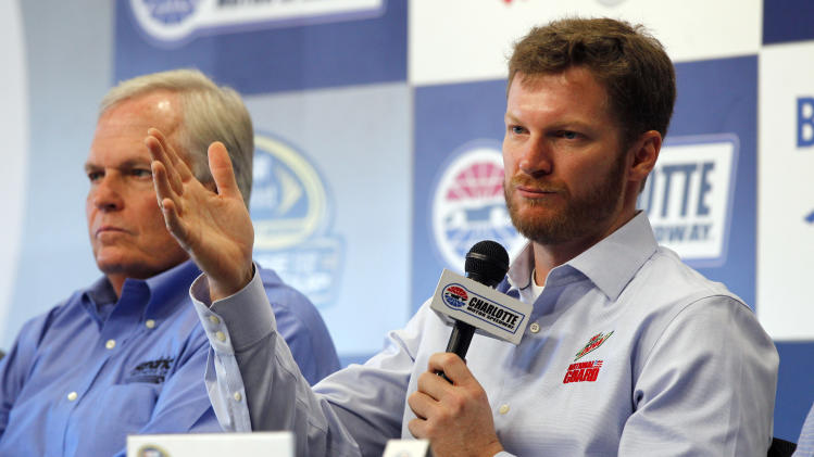 Dale Earnhardt Jr, right, talks about missing the next two races with his second concussion in the past six weeks during a news conference prior to practice for Saturday's NASCAR Bank of America 500 NASCAR Sprint Cup series auto race in Concord, N.C., Thursday, Oct. 11, 2012. Team owner Rick Hendrick, left, looks on. (AP Photo/Chuck Burton)