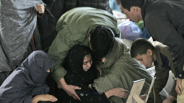 A Pakistani Shiite Muslim woman is comforted while grieving next to the body of her relative, a victim of Saturday's bombing that killed scores of people, as relatives refuse to bury their dead in a protest, in Quetta, Pakistan, Tuesday, Feb. 19, 2013. Pakistan on Tuesday ordered a security operation in response to the weekend bombing targeting minority Shiites that killed 89 people in the southwestern city of Quetta and sacked the top police officer in the surrounding Baluchistan province. (AP Photo/Arshad Butt)