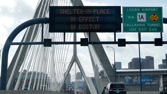 "A message calling for Boston citizens to ""Shelter in Place"" flashes above I-93 on April 19."