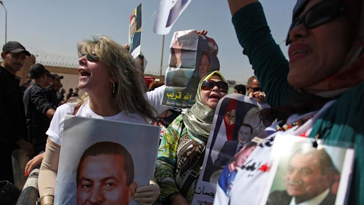 Egyptian supporters of ousted President Hosni Mubarak, pictured, rally outside a courtroom in Cairo, Egypt, Saturday, May 11, 2013. Egyptian prosecutors say they are presenting new evidence in the retrial of Mubarak. The former president, all in white and wearing sunglasses, attended the hearing in the courtroom defendants' cage alongside his two sons and former interior minister, who was in charge of police at the time. (AP Photo/Khalil Hamra)