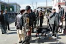 Security officers investigate the scene of a bomb in Gazni, Afghanistan, Saturday, Jan. 26, 2013. A remote co