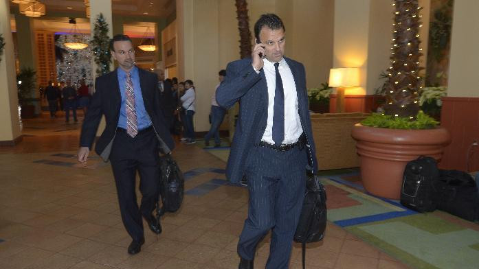 Agent Drew Rosenhaus, right, talks on the phone, while leaving the hotel hosting baseball's winter meetings, in Lake Buena Vista, Fla., Thursday, Dec. 12, 2013