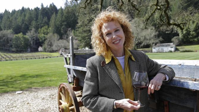 """In this photo taken March 15, 2013 Kate MacMurray, daughter of the late actor Fred MacMurray poses by an old wooden wagon used for diversified farming in World War II and then for cattle at the MacMurray Ranch in Healdsburg, Calif. The former cattle ranch which was purchased in 1941 by the actor in the popular TV series """"My Three Sons,"""" now produces wine and is owned by the Gallo wine family. (AP Photo/Eric Risberg)"""
