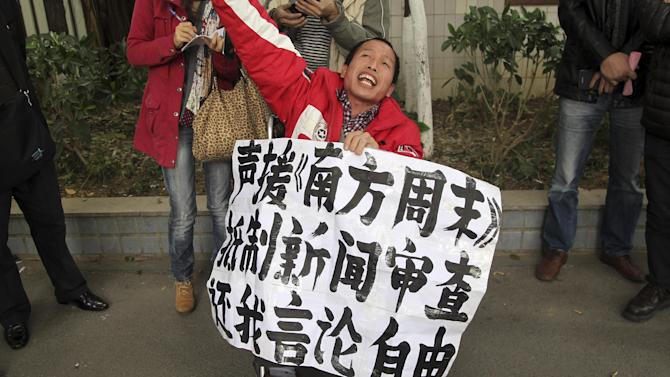 "A supporter of the Southern Weekly newspaper holds up a protest banner which reads ""Support Southern Weekly, boycott news censorship and return my freedom of speech"" outside the newspaper's headquarters in Guangzhou in south China's Guangdong province Tuesday Jan. 8, 2013.  Free-speech protesters in masks squared off against flag-waving communist loyalists in a southern Chinese city Tuesday as a dispute over censorship at a newspaper spilled into the broader population, with authorities shutting microblog accounts of supporters of the paper. (AP Photo) CHINA OUT"