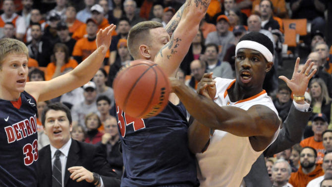 Syracuse's C.J. Fair passes around Detroit's Nick Minnerath as Evan Bruinsma, left, defends during the first half of an NCAA college basketball game in Syracuse, N.Y., Monday, Dec. 17, 2012. (AP Photo/Kevin Rivoli)