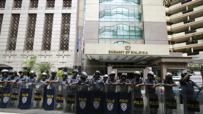 Riot police guard the Malaysian Embassy at the financial district of Makati city east of Manila, Philippines Tuesday March 5, 2013, following a protest against the military assault launched by Malaysian forces against nearly 200 Filipino followers of Sultan Jamalul Kiram of the southern Philippine province of Sulu, who were occupying a Borneo seaside village. Malaysia launched airstrikes and mortar attacks against the Filipinos occupying the village Tuesday to end a bizarre three-week siege that turned into a security nightmare for both Malaysia and the Philippines.   (AP Photo/Bullit Marquez)