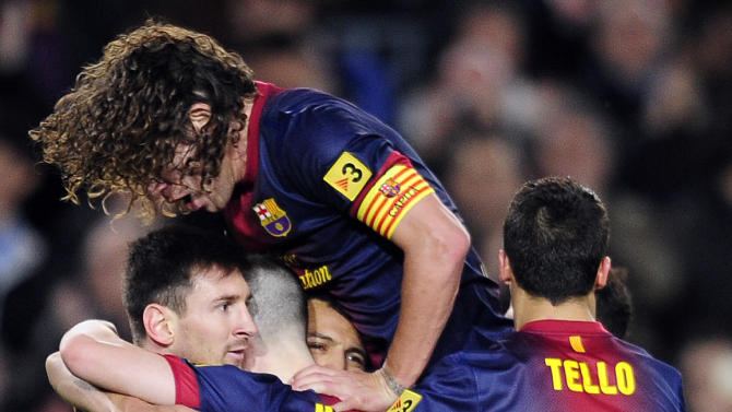 FC Barcelona's Lionel Messi, from Argentina, left, reacts after scoring with his teammate Carles Puyol, top, against Deportivo Coruna during a Spanish La Liga soccer match at the Camp Nou stadium in Barcelona, Spain, Saturday, March 9, 2013. (AP Photo/Manu Fernandez)