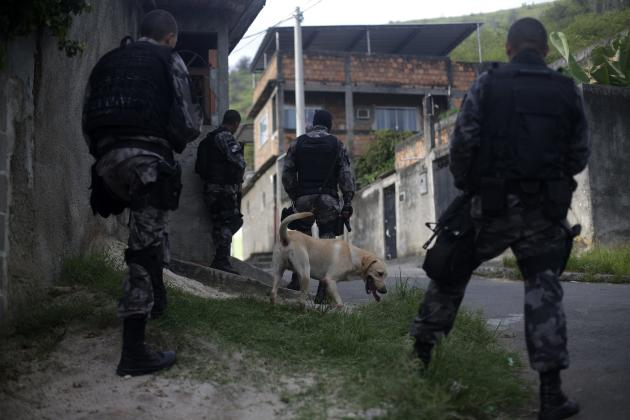 Police officers, with a sniffer dog, take up position at the Vila Kennedy slum during an operation to install the Police Peacekeeping Unit (UPP) in the region in Rio de Janeiro