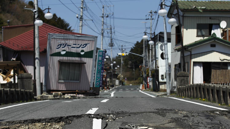 "FILE - This April 17, 2011 file photo shows damage on a street in Futaba, the town where the tsunami crippled Fukushima Dai-ichi nuclear power plant is located, in Fukushima Prefecture, northeastern Japan. After the March 2011 disaster, of all Fukushima communities forced to evacuate, Futaba chose the farthest spot from the nuclear plant - an abandoned high school in Saitama Prefecture, near Tokyo. Atsushi Funahashi, director of ""Nuclear Nation,"" documented a story of the residents of Futaba in the film. The catastrophe in Japan has set off a flurry of independent films telling the stories of regular people who became overnight victims, stories the creators feel are being ignored by mainstream media and often silenced by the authorities. Nearly two years after the quake and tsunami disaster, the films are an attempt by the creative minds of Japan's movie industry not only to confront the horrors of the worst nuclear disaster since Chernobyl, but also as a legacy and to empower the victims by telling their story for international audiences. (AP Photo/Hiro Komae, File)"