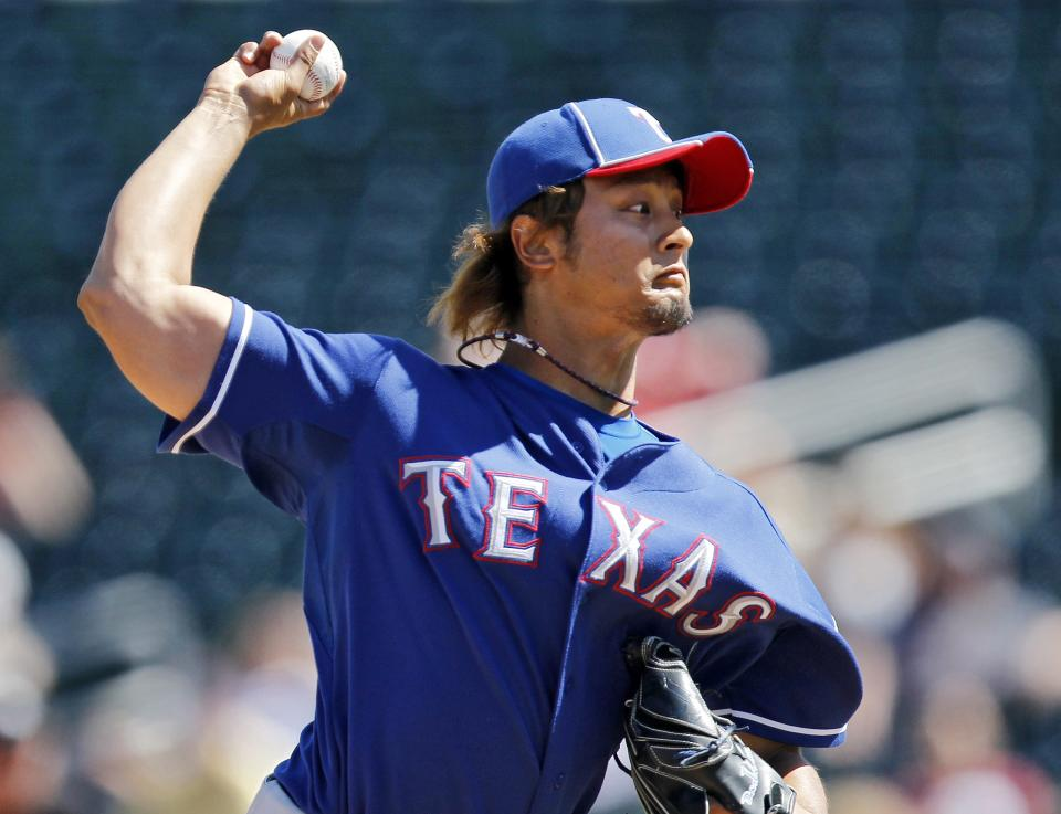 Texas Rangers' Yu Darvish, from Japan, pitches against the Cleveland Indians during the first inning of a spring training baseball game Tuesday, March 13, 2012, in Goodyear, Ariz. (AP Photo/Ross D. Franklin)
