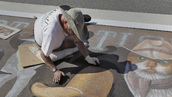 Artist Bryan Moon works on his 3D pavement art project during the Sarasota Chalk Festival Wednesday, Oct. 31, 2012, in Sarasota, Fla. The annual festival begins this week and runs through Nov. 6.(AP Photo/Chris O'Meara)