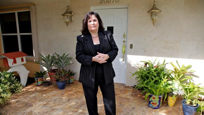 In this Oct. 23, 2012, photo, Hilda Mitrani, 51, of North Miami Beach, Fla.,  poses by her home in Miami. Mitrani has a marketing consulting company and is among many feeling squeezed by a painfully sluggish economic rebound. Unemployment remains high at 7.8 percent. Average pay trails inflation. And the economy is growing too slowly to accelerate hiring. Polls consistently find that the economy is the top concern of voters, and Romney tends to get an edge over Obama when people are asked who might do better with it. Whether that truly drives how Americans vote is a crucial question for Election Day. (AP Photo/Robert Ray)