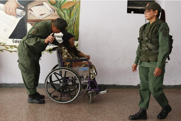 A soldier pushes an elderly woman in wheelchair to polling station during municipal elections in Caracas