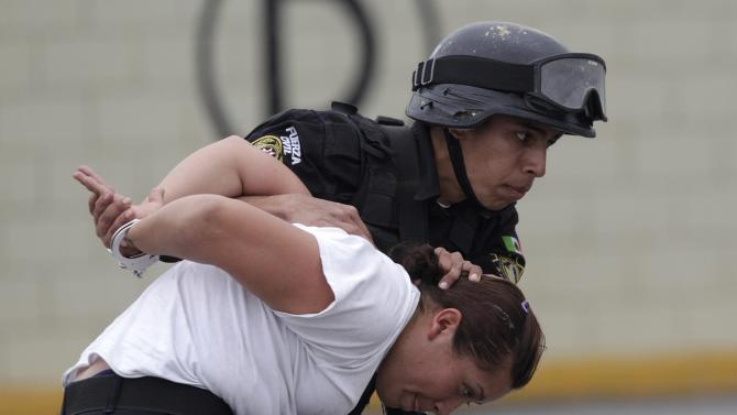 A member of the Fuerza Civil (Civil Force) police unit takes part in a simulated crime situation during a media presentation at the police academy in Monterrey