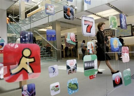 Woman walks past icons for Apple Apps at San Francisco retail store