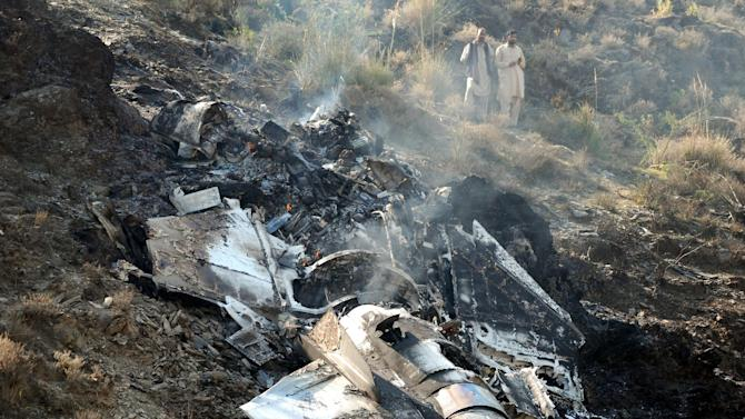FILE - In this Nov. 14, 2011, file photo, villagers stand near wreckage of a Pakistani air force fighter jet that crashed in Attock near Islamabad, Pakistan. Over a dozen Pakistani air force planes have crashed in roughly the past 18 months, raising concerns about the health of an aging fleet that officials are struggling to upgrade because of a lack of funds. A significant number of the air force's combat aircraft are nearly half a century old and have been called on in recent years to help the army fight a domestic Taliban insurgency that has killed thousands of people. This has added to the strain on a force that has historically focused on countering the threat from Pakistan's neighbor and archenemy, India. (AP Photo/Ghulam Shabbir, File)