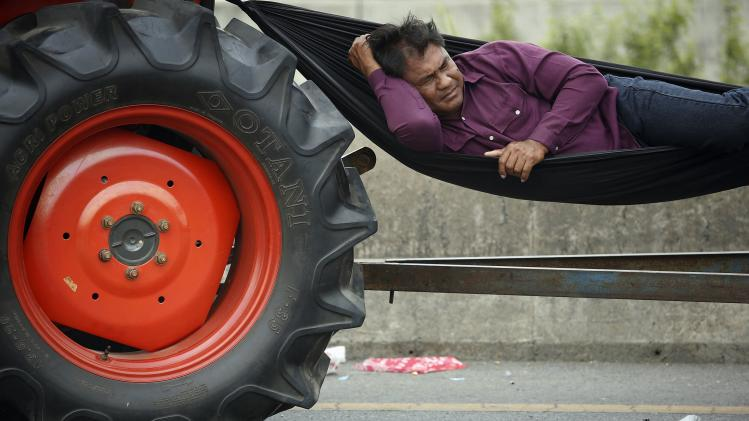 A rice farmer sleeps in a hammock attached to his tractor on a highway where farmers spent a night in Ayutthaya province
