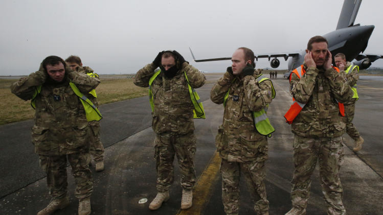 British military personnel protect their ears as a British C17 transport plane lands at the French army base, in Evreux, 90 kms(56 mls)north of Paris, Monday, Jan. 14, 2013. British military equipment was readied for deployment in Mali on Monday as international intervention in the country increased following advances in the north by Islamic extremists with reported links to Al-Qaida. Two C-17 transport planes have arrived at the French military airbase at Evreux, bound for Mali. Two C-17 transport planes have arrived at the French military airbase at Evreux, bound for Mali.  (AP Photo/Michel Euler)