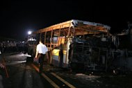 "Investigators are seen at the scene where a bus caught fire on an elevated road in the city of Xiamen, China's southeast Fujian province, on June 7, 2013. An arsonist who wanted to ""vent personal grievances"" is suspected to have caused a horrific bus blaze in China which left 47 people dead, according to state media"