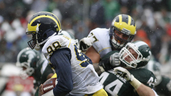 Michigan quarterback Devin Gardner (98) runs on a keeper in front of Michigan State's Marcus Rush (44) and Taylor Lewan (77) during the second quarter of an NCAA college football game, Saturday, Nov. 2, 2013, in East Lansing, Mich. (AP Photo/Al Goldis)