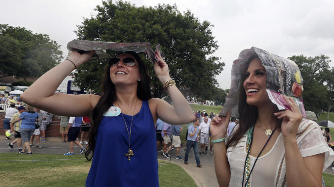 Liz Shepard, left, and Lauren Whitlle laugh as they uses their pairing sheets to keep a light drizzle off her heads during a weather delay in the second round of the Colonial golf tournament Friday, May 24, 2013, in Fort Worth, Texas.  Play was suspended due to lightning in the area. (AP Photo/LM Otero)