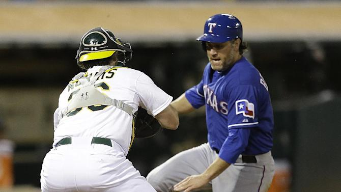 Texas Rangers' Lance Berkman, right, can't avoid the tag by Oakland Athletics catcher Derek Norris in the sixth inning of a baseball game Tuesday, May 14, 2013, in Oakland, Calif. (AP Photo/Ben Margot)