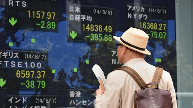 A man looks at a stock market board in Tokyo on August 8, 2014