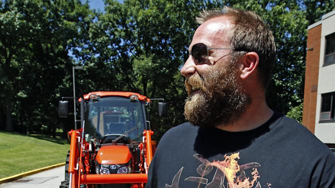 Pittsburgh Steelers defensive lineman Brett Keisel, right, walks away from the tractor he drove for his arrival for NFL football training camp at the team's training facility in Latrobe, Pa., Wednesday, July 25, 2012. (AP Photo/Keith Srakocic)