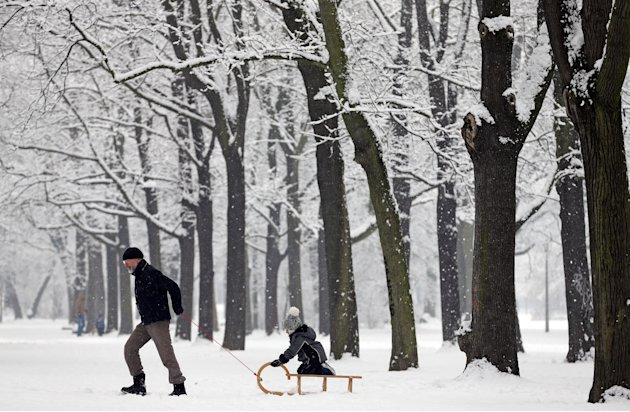A man pulls a child on a sled in a snowy park in Leipzig, Germany, Good Friday March 29, 2013. Weather forecasts predict a snowy and cold Easter weekend.  (AP Photo/dpa,Jan Woitas)