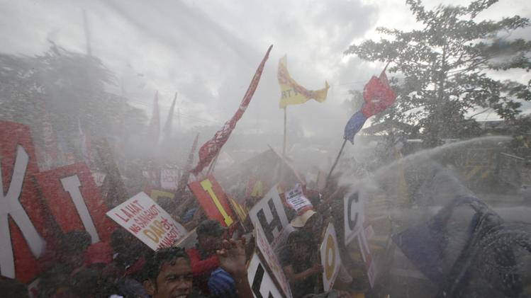 Protesters are dispersed with water cannon as they attempt to force their way closer to the House of Representatives to coincide with the State of the Nation Address by Philippine President Benigno Aquino III Monday, July 28, 2014 at suburban Quezon city, northeast of Manila, Philippines. Aquino is expected to tackle in his address, the controversial Disbursement Acceleration Program (DAP), the allocation of funds or savings by the Government to finance various programs or projects which is under the discretion of the President and was declared in part as unconstitutional by the Supreme Court. (AP Photo/Bullit Marquez)