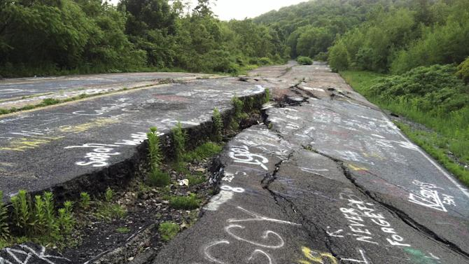 In this May 24, 2012 photo, Route 61 is shown eroded and covered in graffiti in Centralia, Pa. Fifty years ago on Sunday, May 27, 2012, a fire at the town dump spread to a network of coal mines underneath hundreds of homes and business in the northeastern Pennsylvania borough of Centralia, eventually forcing the demolition of nearly every building. (AP Photo/Michael Rubinkam)
