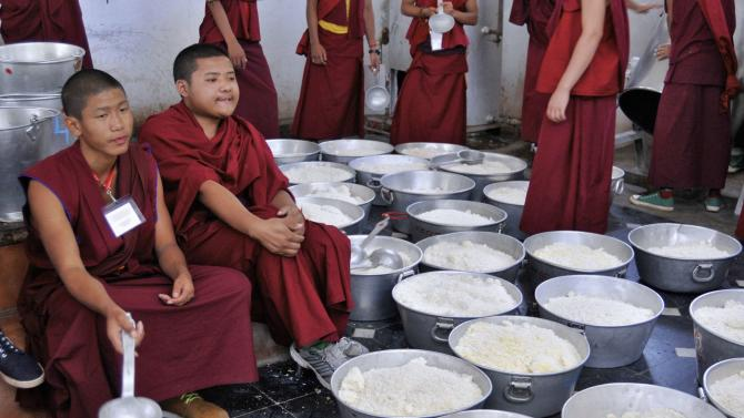 Buddhist monks wait to serve cooked rice to attendees of the Jangchup Lamrim teachings at Gaden Jangtse Thoesam Norling Monastery in Mundgod