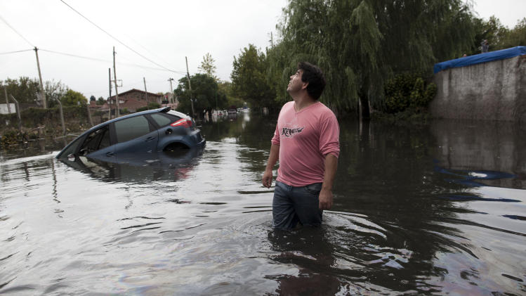 A man looks to the sky outside his home in a flooded street where a car is submerged in La Plata, in Argentina's Buenos Aires province, Wednesday, April 3, 2013. At least 35 people were killed by flooding overnight in Argentina's Buenos Aires province, the governor said Wednesday, bringing the overall death toll from days of torrential rains to at least 41 and leaving large stretches of the provincial capital under water. (AP Photo/Natacha Pisarenko)