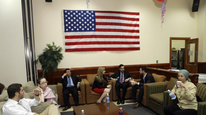 FILE - In this Nov. 7, 2012 file photo. U.S. embassy staff sit under a national flag at the U.S. Embassy in Baghdad, Iraq. The U.S. Embassy is cutting staff sharply a decade after the war in Iraq began. As recently as a year ago, the immense U.S. Embassy in Baghdad and other sites around the country were staffed by more than 16,000 employees. Today, that number has fallen to about 10,500. (AP Photo/ Khalid Mohammed, File)
