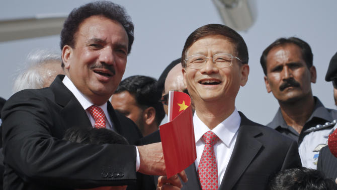Chinese Public Security Minister Meng Jianzhu, second right, and Pakistani Interior Minister Rehman Malik, left, wave Chinese flag upon Jianzhu's arrival at Chaklala airbase in Rawalpindi, Pakistan on Monday, Sept. 26, 2011. China's top security official is visiting Pakistan for talks focusing on increased cooperation against Chinese militants who have found sanctuary in the northwest of the country. (AP Photo/Anjum Naveed)