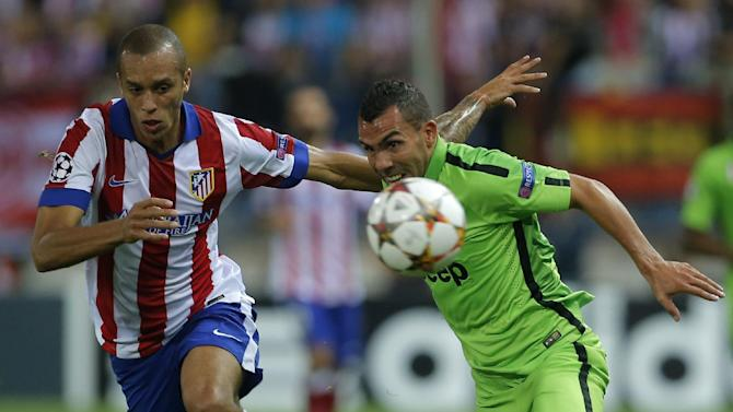 Atletico's Joao Miranda, left and Juventus' Carlos Tevez chase the ball during the Group A Champions League soccer match between Atletico de Madrid and Juventus at the Vicente Calderon stadium in Madrid, Spain, Wednesday Oct. 1, 2014