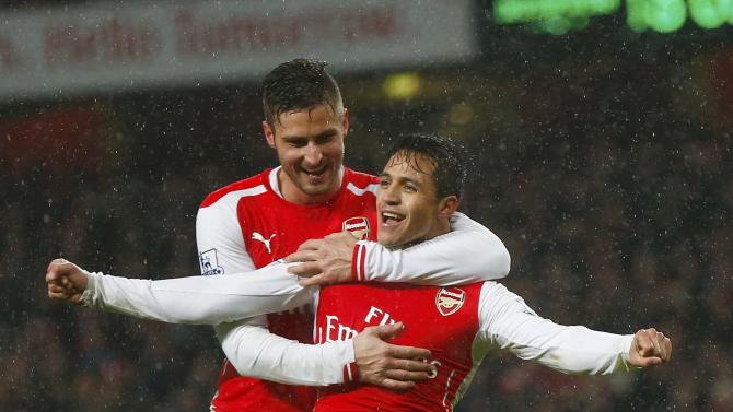Arsenal's Alexis Sanchez celebrates with team-mate Olivier Giroud after scoring a goal against Queens Park Rangers' during their English Premier League soccer match at the Emirates Stadium in London