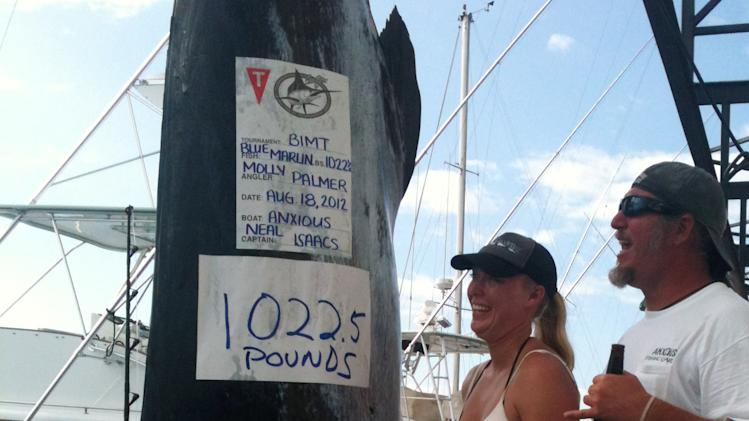 In this Aug. 18, 2012 photo provided by Jody Bright, Molly Palmer stands with her husband Shawn Palmer near her catch_ a 12-foot marlin that took more than four hours to get on her team's boat, weighing it at more than a half-ton _ a would-be world record, in Kailua-Kona, Hawaii. (AP Photo/Courtesy Jody Bright)