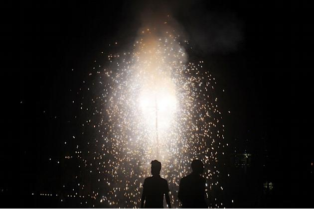 Revellers watch fireworks at a park during Diwali, the festival of lights, in Kolkata on November 13, 2012. The festival marks the victory of good over evil and commemorates the time when Hindu God Lo