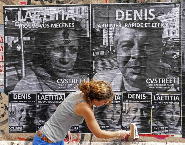 Laetitia, a 30-year-old unemployed Frenchwoman and member of CVStreet group, pastes posters of herself and others unemployed people in the streets of Marseille