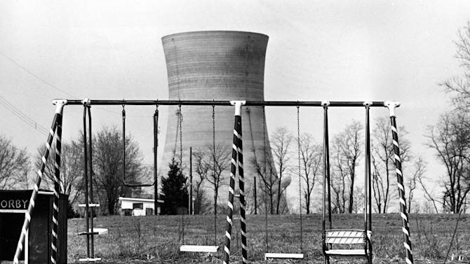 FILE - In this March 30, 1979 file photo, a cooling tower at the Three Mile Island nuclear power plant near Harrisburg, Pa., looms behind an abandoned playground. Japan's Fukushima disaster, which will leave taxpayers there with a massive bill, brings to the fore one of the industry's key weaknesses _ that nuclear power is a viable source for cheap energy only if it goes uninsured. (AP Photo/Barry Thumma, file)