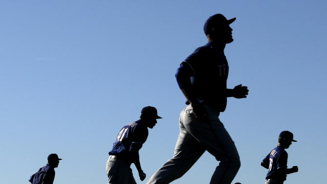 Texas Rangers players run during a spring training baseball workout, Thursday, Feb. 14, 2013, in Surprise, Ariz. (AP Photo/Charlie Riedel)