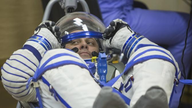 ISS crew Shkaplerov adjusts his helmet during a space suit check at the Baikonur cosmodrome