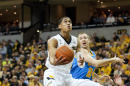 Missouri's Jordan Clarkson, left, shoots as he drives past UCLA's Travis Wear, right, during the first half of an NCAA college basketball game Saturday, Dec. 7, 2013, in Columbia, Mo. (AP Photo/L.G. Patterson)